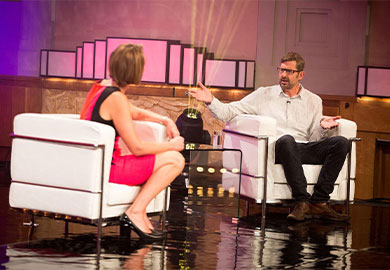 Lucy Hocking interviewing Louis Theroux on white chairs