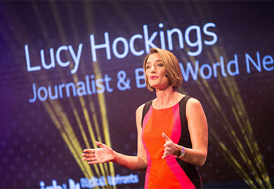 BBC Journalist, Lucy Hockings, wearing an orange dress and giving an opening speech